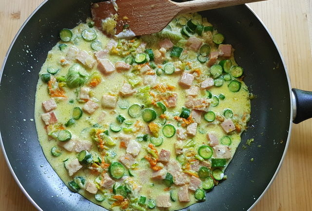 sauce in frying pan for pasta with zucchini flowers, saffron and ham