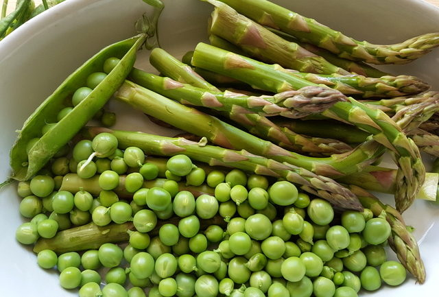 shelled fresh peas and fresh asparagus in white bowl