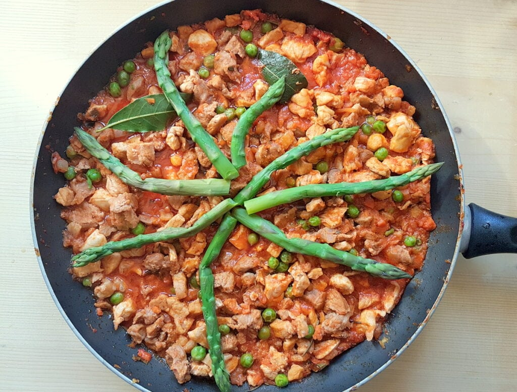ready spring mixed meat ragu with cooked asparagus in skillet