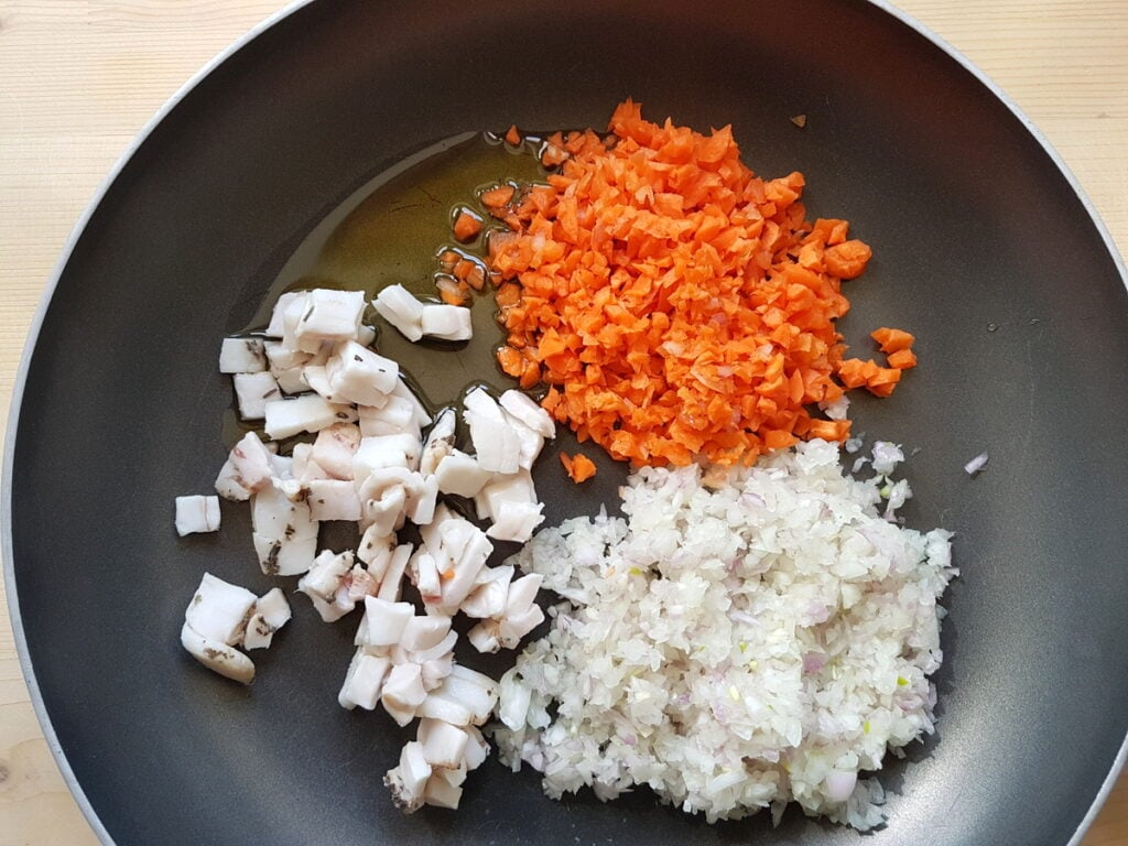 chopped lardo, carrots and onions in skillet with olive oil