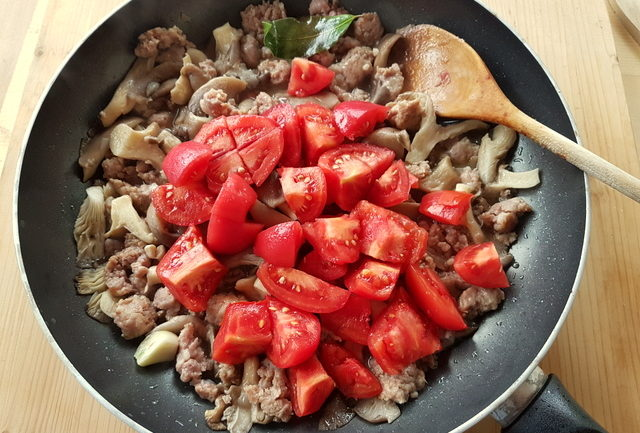 chopped peeled tomatoes, oyster mushrooms and sausage meat in frying pan