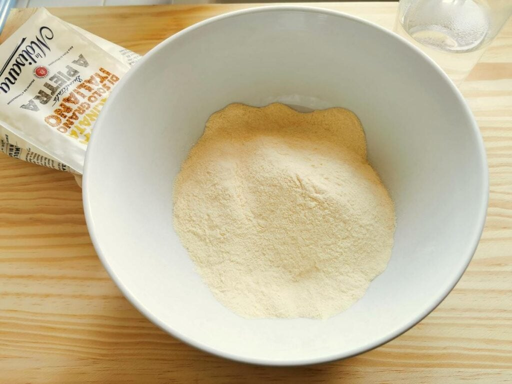 semolina flour in white bowl and salted water in a glass