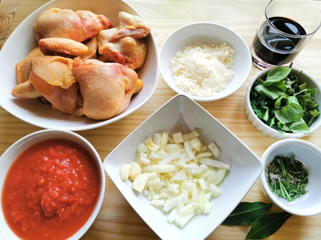 chopped onions and garlic in white bowl. Chopped herbs in white bowl and quartered chicken in white bowls. Plus tomato pulp in white bowl
