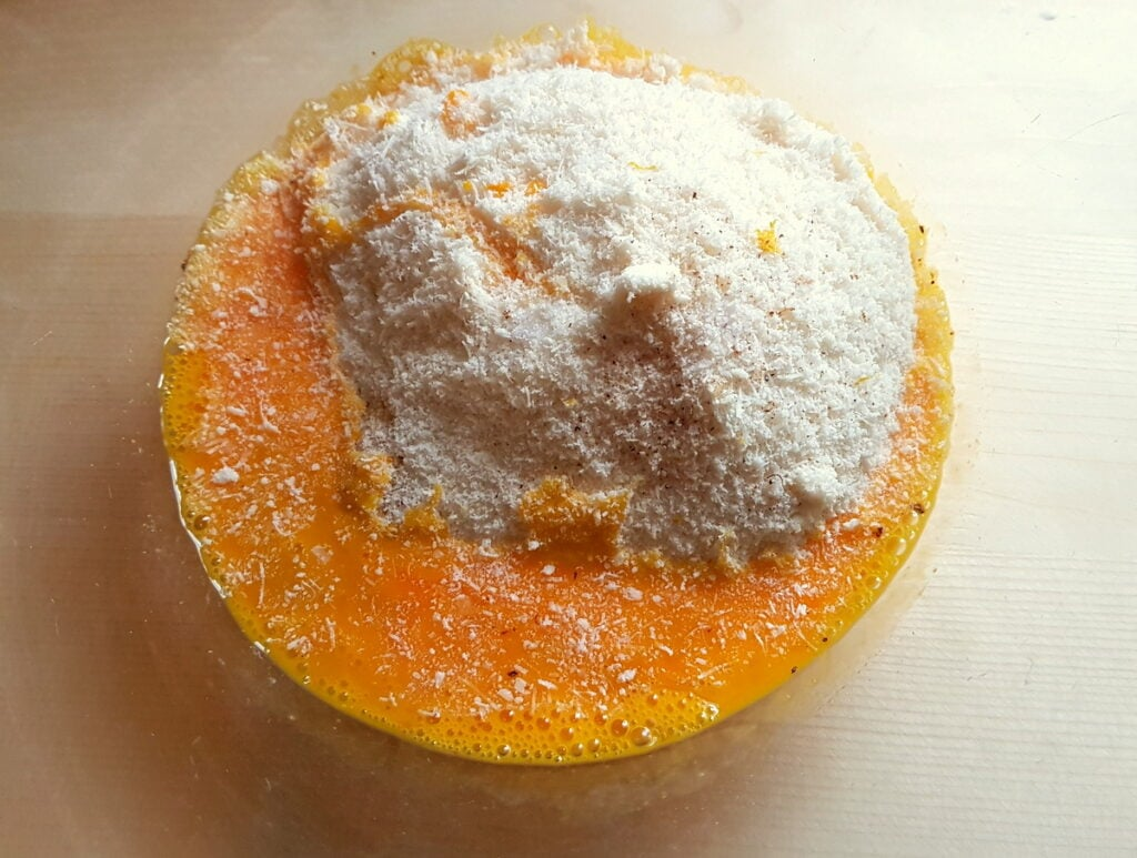 beaten eggs, breadcrumbs and cheese in glass bowl