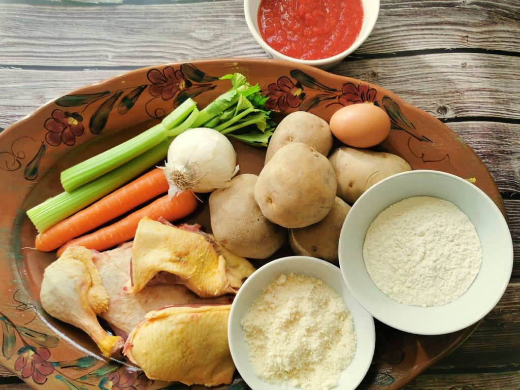 ingredients for homemade potato gnocchi with duck ragu on oval terracotta plate