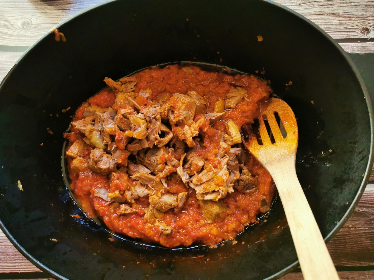 Duck meat removed from bones and added back to the sauce in Dutch oven.