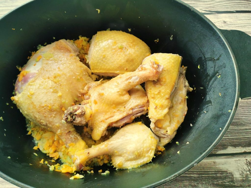 duck pieces in Dutch oven with vegetables