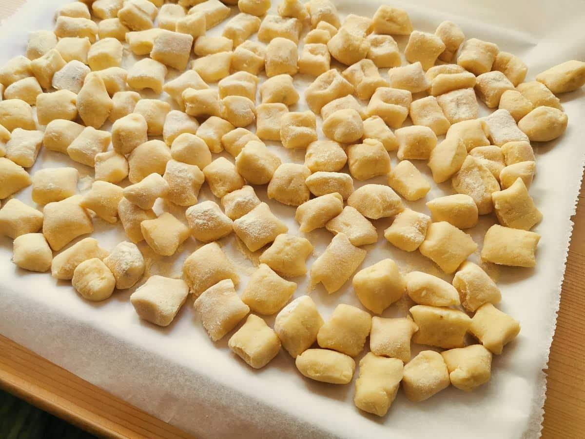 Ready uncooked potato gnocchi on floured tray