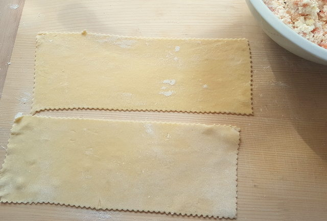 2 rolled out fresh pasta rectangles on wooden board