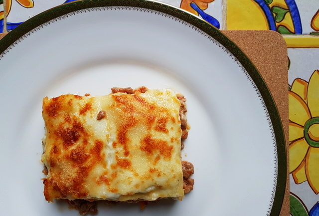 a serving of lasagne al forno with bolognese on white plate with green rim