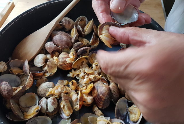 removing cooked clams from their shells for pasta alle vongole