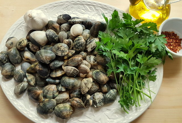 Ingredients for pasta alle vongole on a white plate