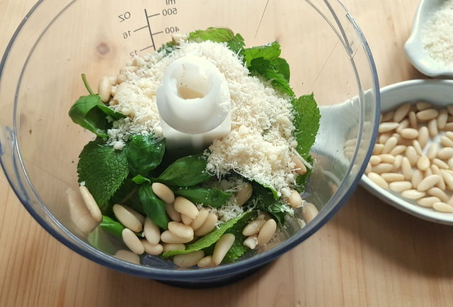Fresh mint and basil leaves, pine nuts and grated Parmesan in food blender