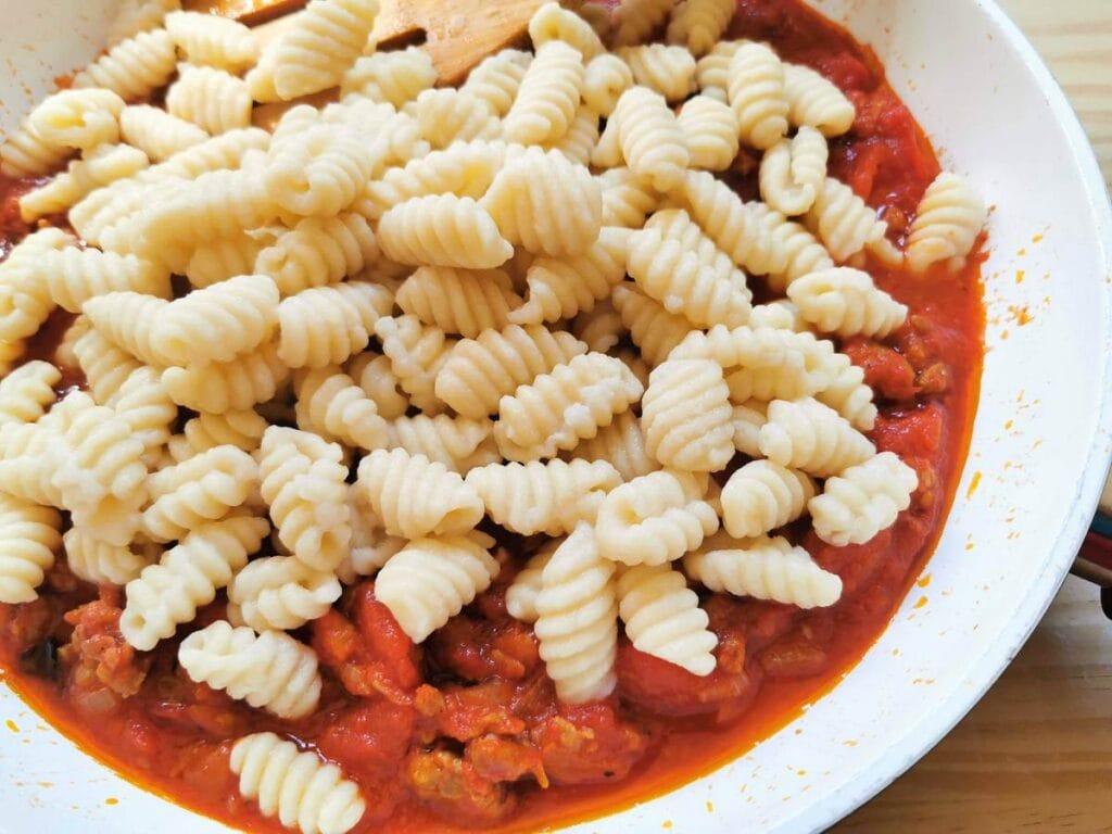 Cooked Sardinian gnocchi - malloreddus added to sausage sauce in pan.