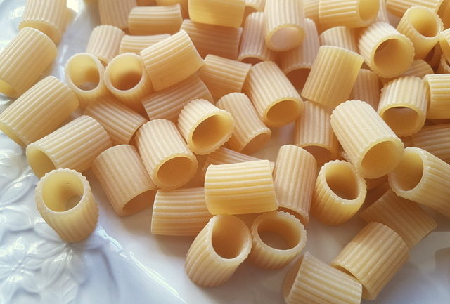 close up of mezze maniche pasta tubes on white plate