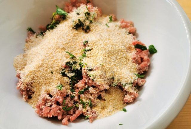 ground beef and pork, breadcrumbs, grated cheese and parsley in white bowl