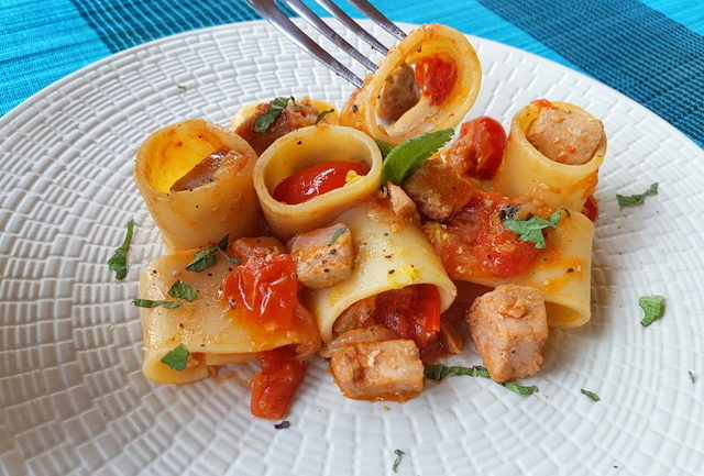 mezzi paccheri with fresh tuna ragu on white plate