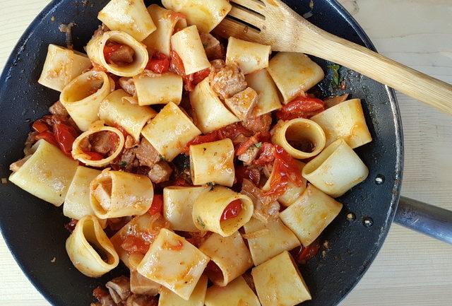 organic mezzi paccheri pasta mixed with fresh tuna ragu in skillet