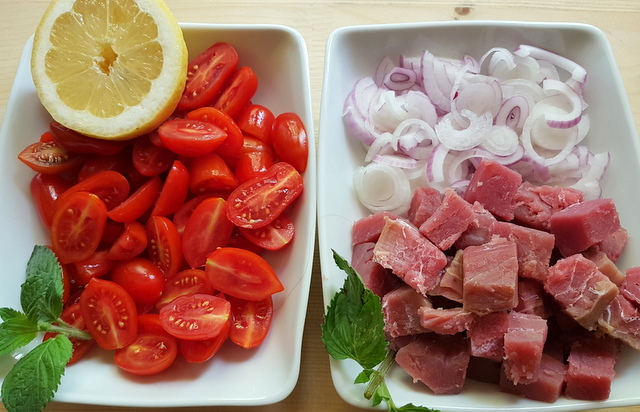 sliced red onions and cubed tuna in white bowl plus halved date tomatoes and half a lemon in another white bowl.