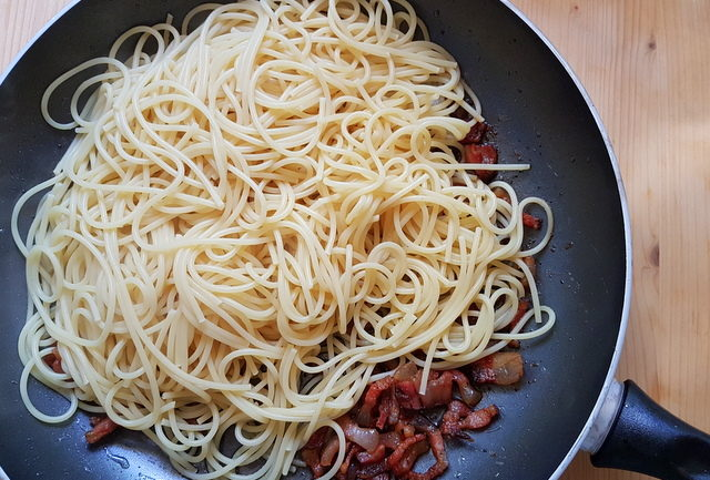 cooked spaghetti and guanciale in frying pan