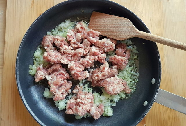 crumbled sausage and chopped onion in frying pan