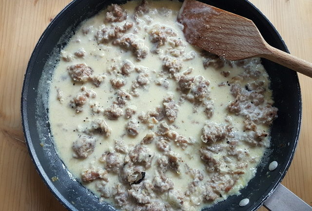 sausage meat and cream pasta sauce cooking in frying pan