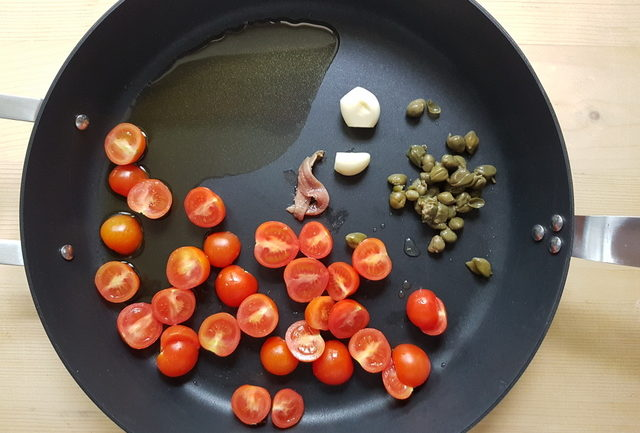 cherry tomato halves, anchovies, garlic and capers in frying pan
