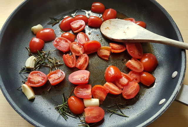garlic, rosemary and cherry tomatoes in frying pan