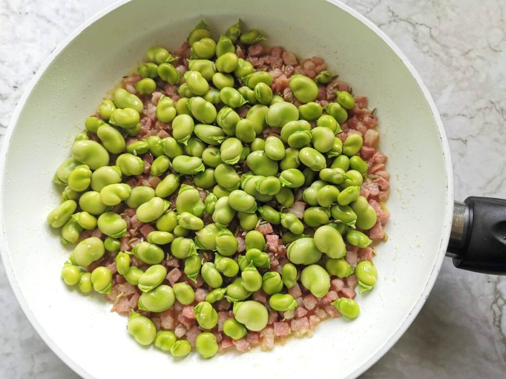 shelled fava beans in pan with cooked pancetta and garlic