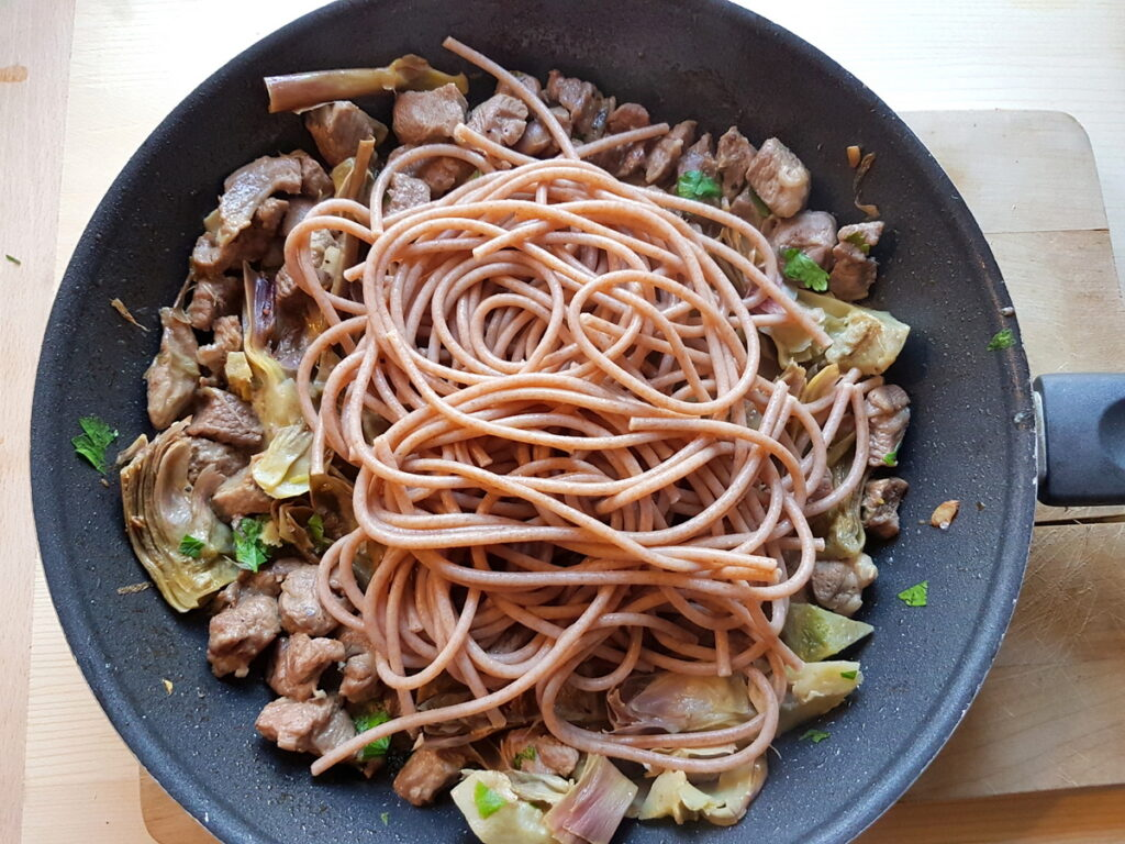 whole-wheat spaghettoni pasta with lamb and artichokes in skillet