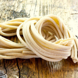 fresh pici pasta nests on wooden table