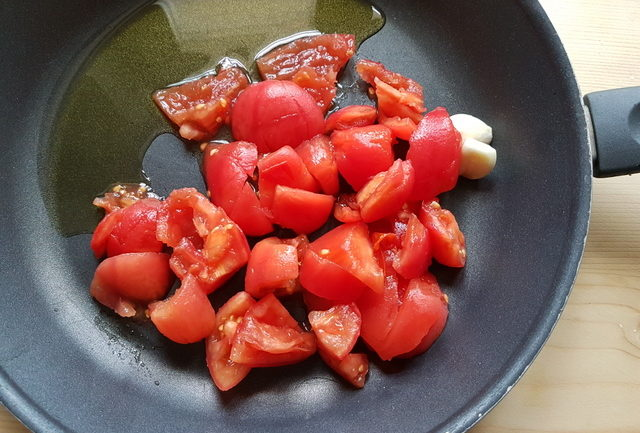 peeled and chopped fresh tomatoes in frying pan with garlic and olive oil
