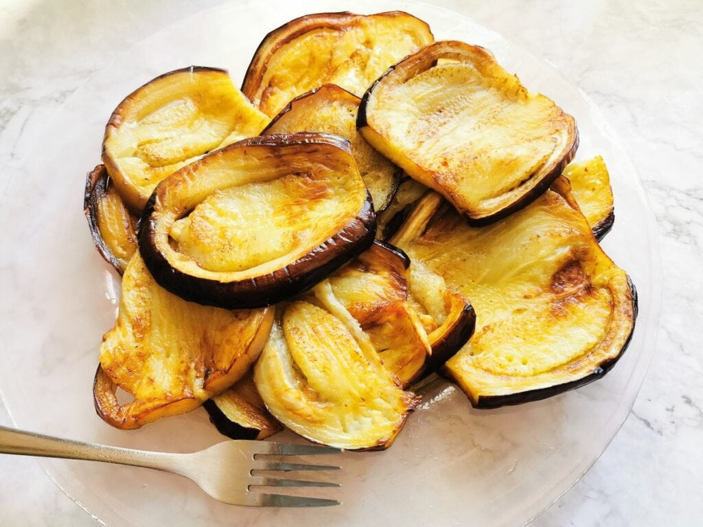 Fried eggplant slices on glass plate.