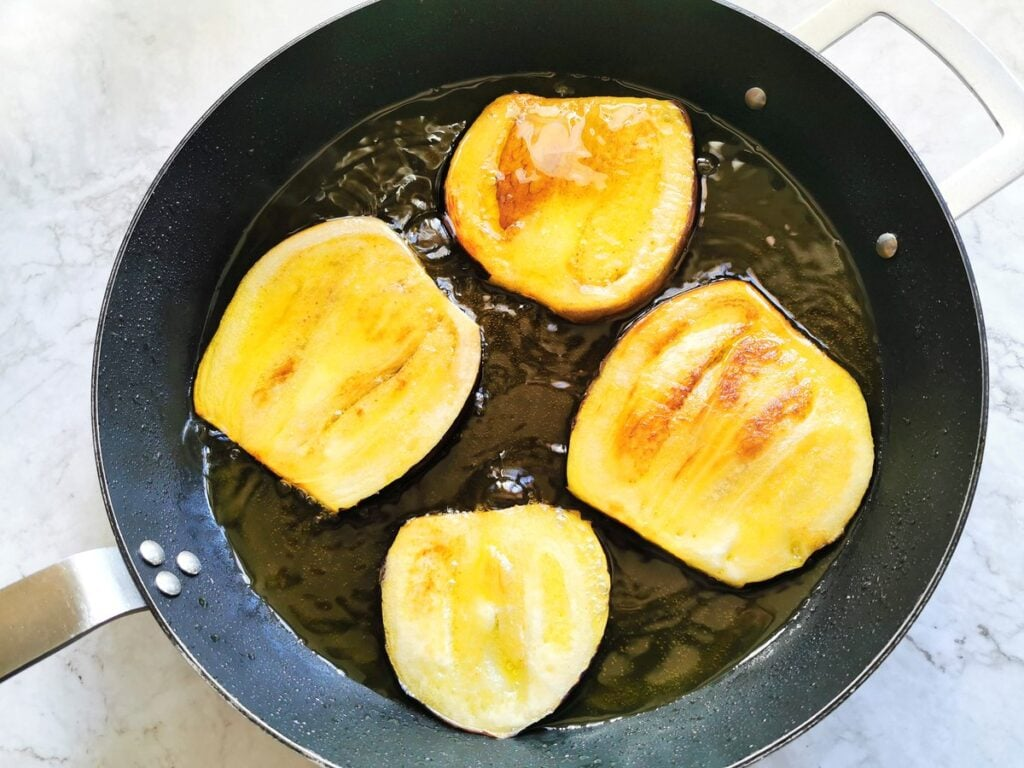 egglant slices cooking in olive oil in  frying pan