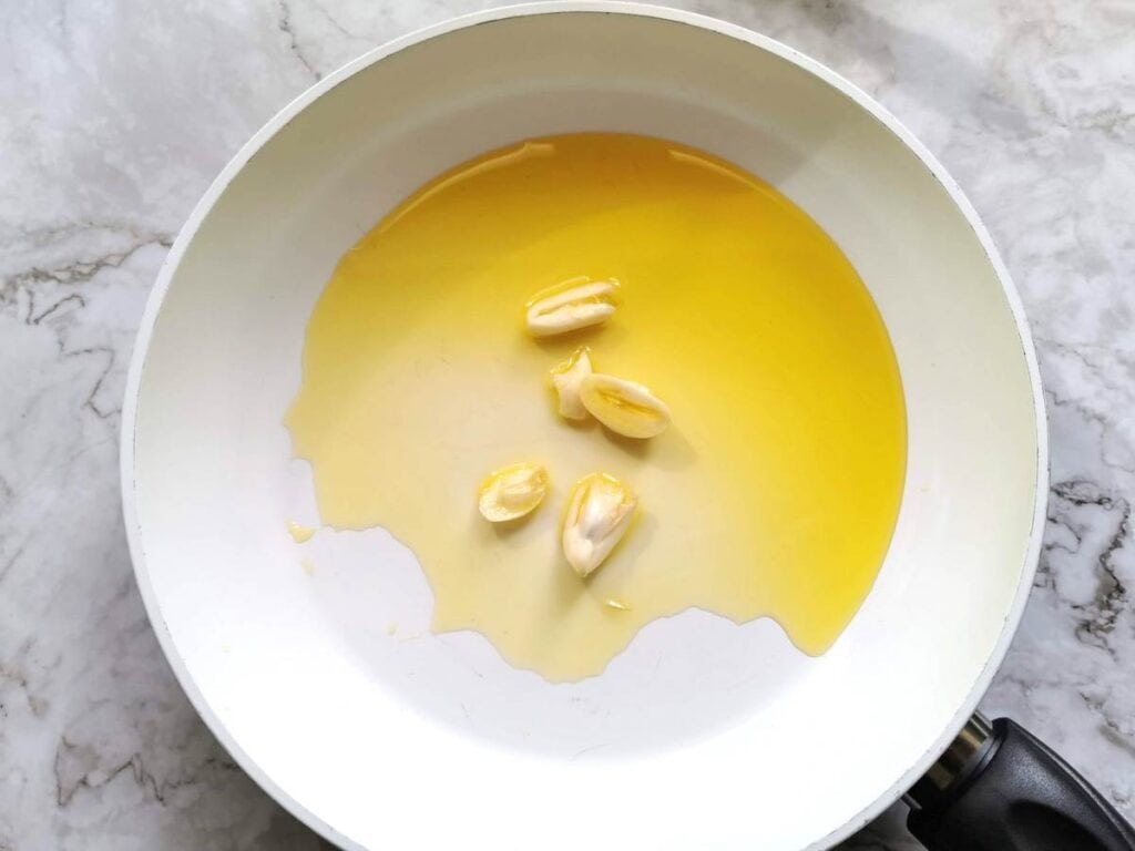 Peeled garlic cloves cooking in olive oil  in frying pan