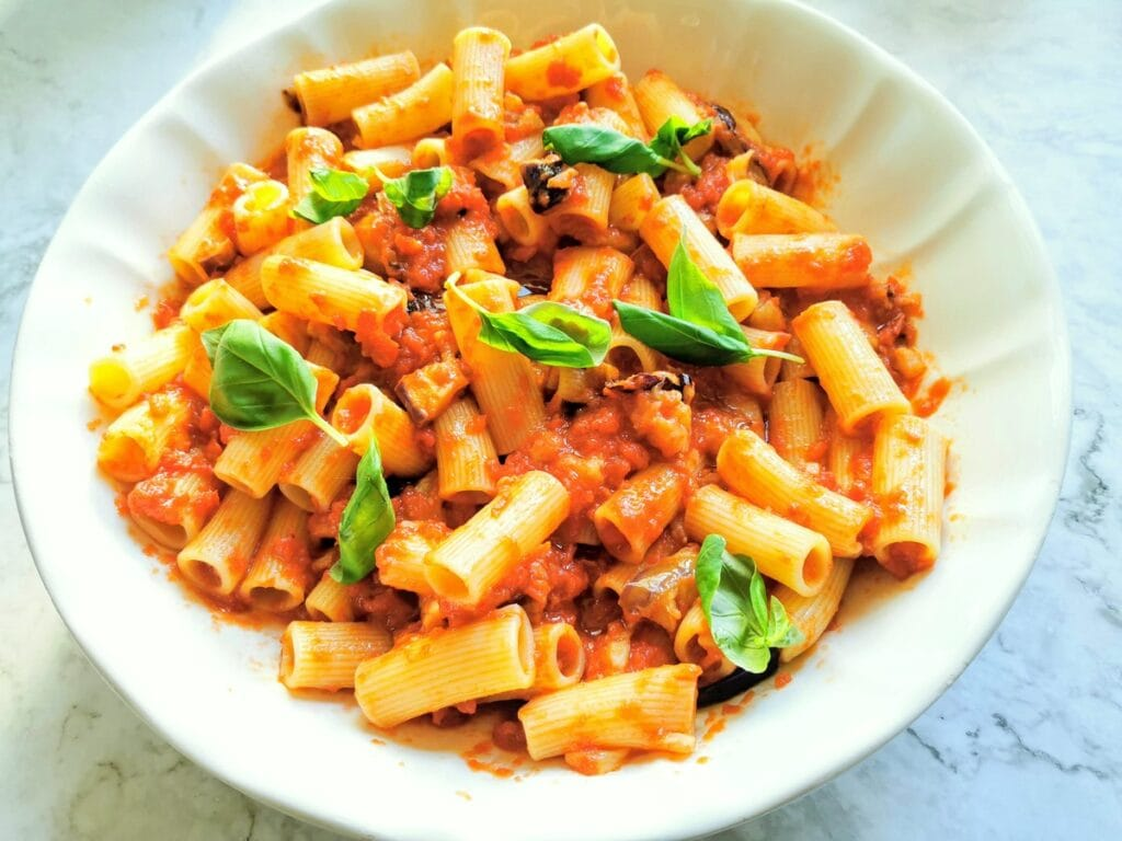 Cooked pasta in a bowl mixed with tomato and eggplant sauce with basil leaves on top