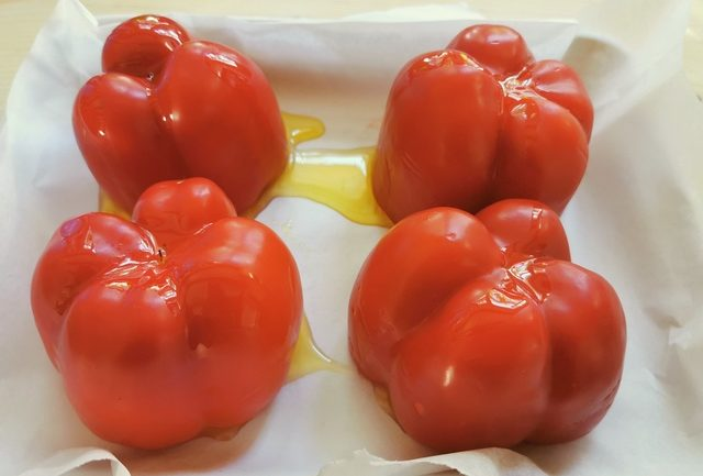 red peppers on baking tray with olive oil