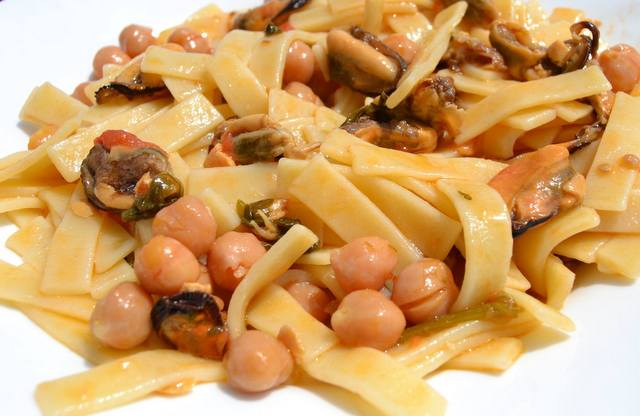 sagne pasta with chickpeas and mussels in white bowl