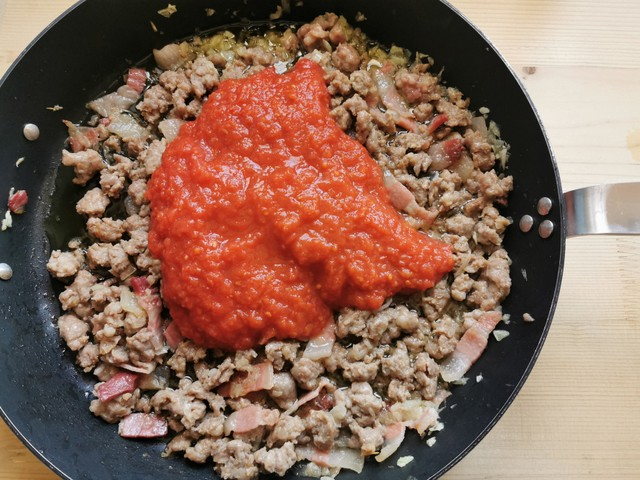 tomato passata added to skillet with sausage, guanciale and onion