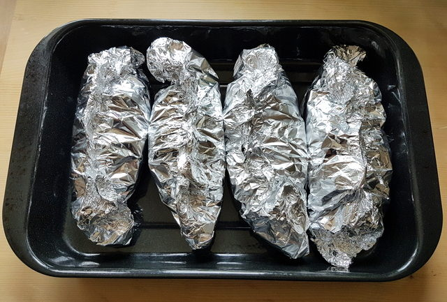 4 portions of seafood linguine al cartoccio wrapped in foil