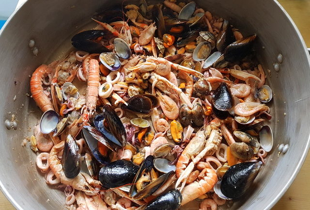 Mussels, clams, scampi, shrimps and calamari cooking in large pot