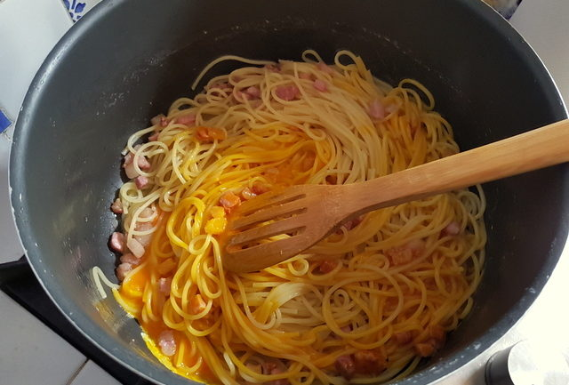 mixing pasta and eggs for spaghetti alla carbonara