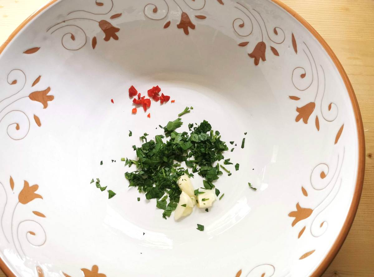 crushed garlic, chopped parsley and peperoncino in a large white bowl