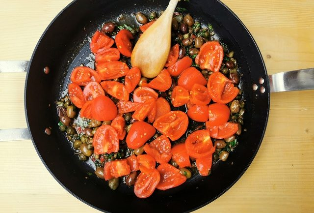 peeled and chopped tomatoes cooking with other puttanesca ingredients in skillet