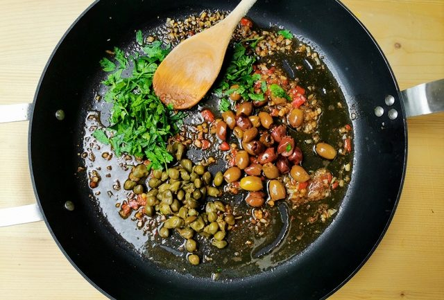 olives, capers, parsley, anchovies, garlic and peperoncino cooking in skillet