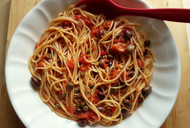 spaghetti alla puttanesca in white serving bowl