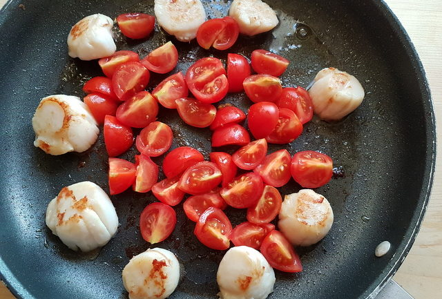 scallops and cherry tomatoes cooking in frying pan