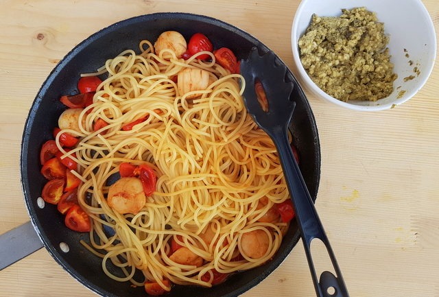 spaghetti, scallops and tomatoes in frying pan with almon, caper, citrus fruit pesto