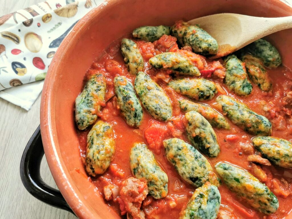 cooked  spinach gnocchi in serving bowl with lamb ragu