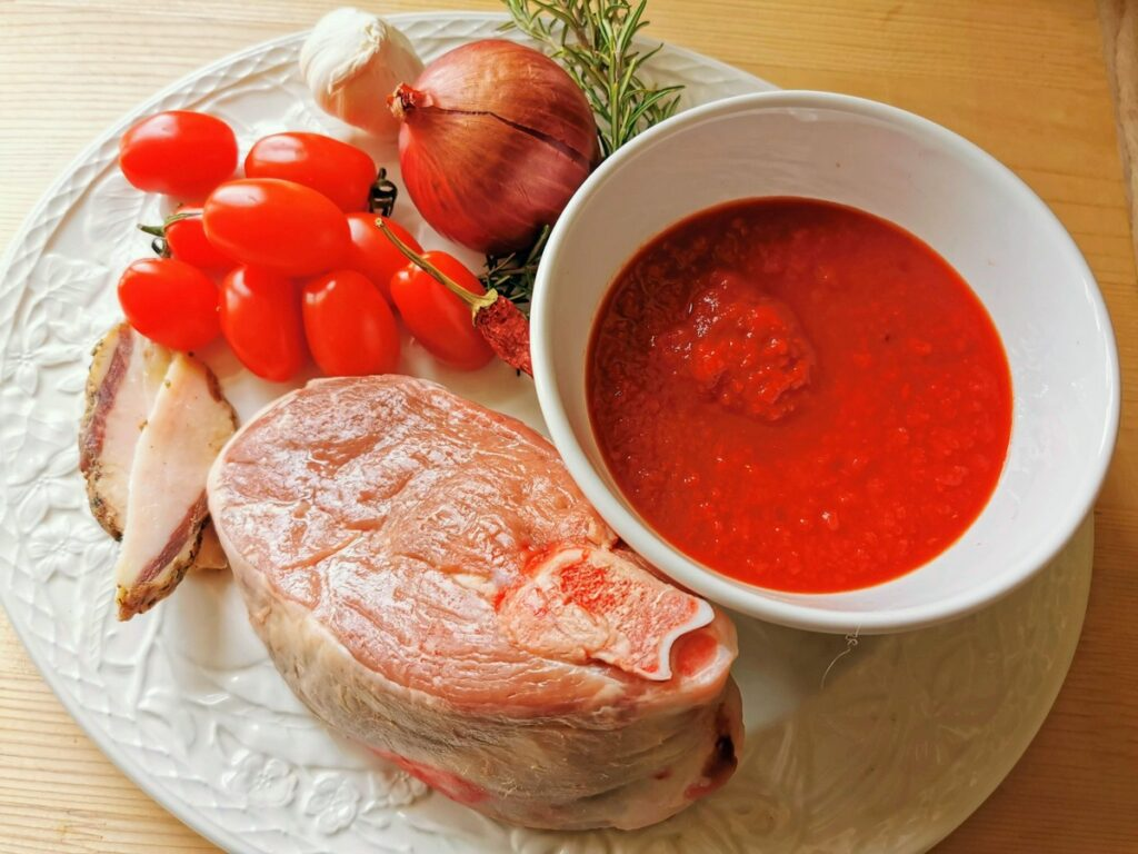 ingredients for lamb ragu on white plate.